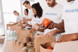 Volunteers putting foods in bag for donation.