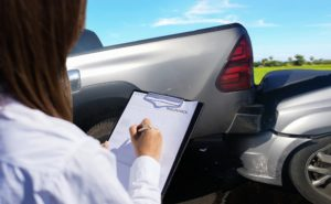 Car insurance agent thoroughly inspecting car damages.